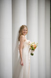Smiling bride against a row of columns Royalty Free Stock Photos