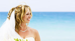 A smiling bride on the beach. A smiling bride with a beautiful ocean background Royalty Free Stock Photo