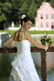 Smiling bride with bouquet. Smiling bride in half body portrait holding bouquet of flowers. She is turning to look over her shoulder Stock Image