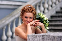 Smiling bride with bouquet. Half body portrait of smiling auburn bride holding wedding bouquet Stock Images