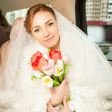 Smiling bride with bouquet on backseat of car Stock Photos