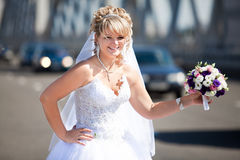 Smiling bride with bouquet standing on highway Stock Photo