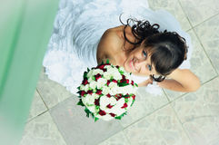 Smiling bride with bunch of flowers to upward looking Stock Photos