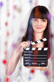 Smiling bride with clapper board Stock Photo