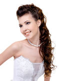 Smiling bride with curly wedding hairstyle. Beautiful young smiling bride with modern wedding hairstyle - long curly hairs Royalty Free Stock Photo