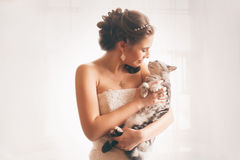 Smiling bride embracing cat Stock Photo