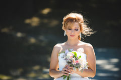 Smiling Bride with Flowers. Smiling bride looking at flowers at sunny day Royalty Free Stock Photo