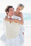 Smiling bride getting a piggy back from husband Royalty Free Stock Image