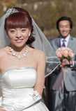 Smiling bride with groom in background (2) Royalty Free Stock Photo