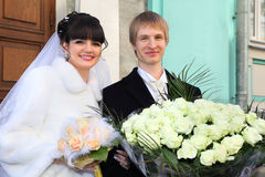 Smiling bride and groom with bouquets Royalty Free Stock Images