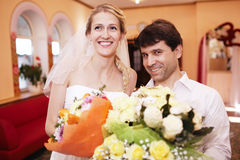 Smiling bride and groom with bouquets of flowers royalty free stock images