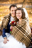 Smiling bride and groom covering by plaid at park Stock Photo