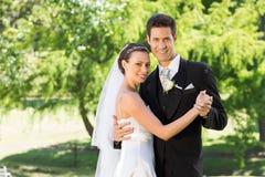 Smiling bride and groom dancing in garden Stock Image