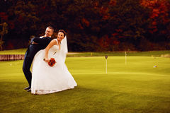 Smiling bride and groom on golf field Royalty Free Stock Photos