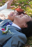 Smiling bride and groom on ground Stock Photo