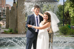 Smiling bride and groom hugging next to fountain at park Royalty Free Stock Photography