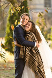 Smiling bride and groom hugging under plaid at autumn park Royalty Free Stock Image