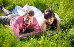 Smiling bride and groom lying on field at summer Royalty Free Stock Image