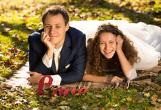 Smiling bride and groom lying on grass at autumn park Royalty Free Stock Photo