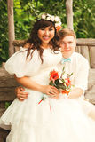 Smiling bride and groom sitting on wooden bench Stock Photos