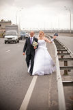 Smiling bride and groom walking on empty highway Royalty Free Stock Photography