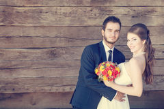 Smiling bride and groom on wooden background Stock Photos