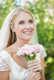 Smiling bride holding her bouquet wearing a veil looking up Royalty Free Stock Photo