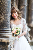 Smiling bride holding wedding bouquet on background of old building with columns, close-up Royalty Free Stock Photo