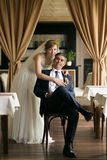 Smiling bride hugging groom from back at restaurant Royalty Free Stock Images