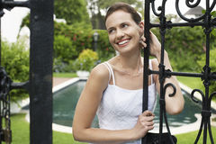 Smiling Bride Leaning On Garden Gate Stock Images