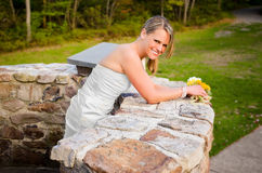 Smiling Bride leaning on Stone Wall Royalty Free Stock Photo