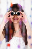 Smiling bride looks through binoculars Royalty Free Stock Images
