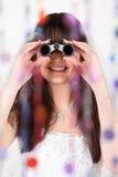Smiling bride looks through binoculars Royalty Free Stock Images