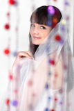 Smiling bride looks at camera. Smiling beautiful bride looks at camera behind transparent curtain of beads; focus on woman Royalty Free Stock Photos