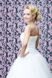 Smiling bride portrait. 20s yeared bride in white dress is looking back over the shoulder with smile on her face Royalty Free Stock Images