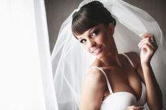 Smiling bride is posing  in whiteness on the background  wall.  Stock Photo