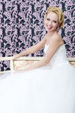 Smiling bride put out her toungue sitting bench Royalty Free Stock Photography