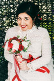 Smiling bride with red bouquet in cane chair Royalty Free Stock Photography