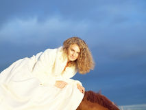 Smiling bride ride on horse at dramatic sky backgr. Bride ride on red  horse in gulf at evening sunset Stock Images