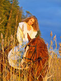 Smiling bride ride on horse in field at evening. Bride ride on red  horse in field at evening sunset Royalty Free Stock Images