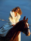 Smiling bride ride on horse in gulf at evening. Bride ride on red  horse in gulf at evening sunset Stock Photography