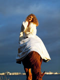Smiling bride ride on horse in gulf at evening Stock Images