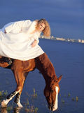 Smiling bride ride on horse in gulf at evening Stock Photo