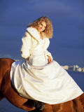 Smiling bride ride on horse in gulf at evening Stock Image