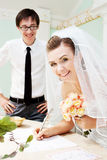 Smiling bride signing marriage papers Royalty Free Stock Photography