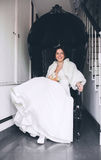 Smiling bride sitting in black chair. In hall Stock Photography