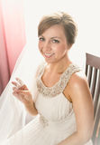 Smiling bride sitting on chair next to window at bedroom Royalty Free Stock Images