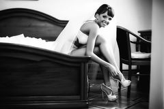 Smiling bride is sitting and wearing high hils Stock Photos