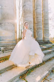 Smiling bride is spinning in the pompous wedding dress standing on the stair of the old antique building. Stock Photography