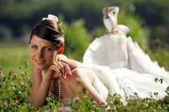 Smiling bride in summer meadow. Close up of smiling bride in traditional white dress lying in meadow of flowers, summer scene royalty free stock photo